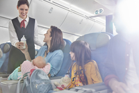 Smiling flight attendant bringing baby bottle to mother with baby on airplane 11086037974| 写真素材・ストックフォト・画像・イラスト素材|アマナイメージズ