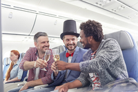 Young male friends toasting champagne glasses in first class on airplane 11086037993| 写真素材・ストックフォト・画像・イラスト素材|アマナイメージズ