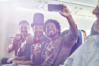 Enthusiastic young male friends with camera phone drinking and taking selfie on airplane 11086038001| 写真素材・ストックフォト・画像・イラスト素材|アマナイメージズ