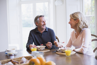 Smiling mature couple eating breakfast and talking at dining table 11086039098| 写真素材・ストックフォト・画像・イラスト素材|アマナイメージズ