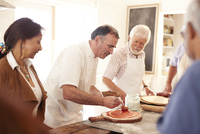 Senior friends watching chef spreading marinara sauce on pizza dough in cooking class 11086040522| 写真素材・ストックフォト・画像・イラスト素材|アマナイメージズ