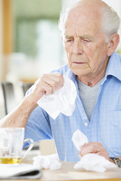 Older man with cold wiping his nose