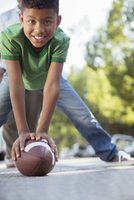 Portrait of smiling boy preparing to snap football
