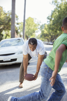 Grandfather and grandson playing football in street