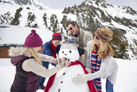Family building a snowman together