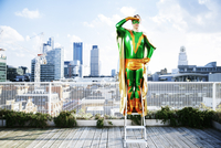 Superhero overlooking view from stepladder on city rooftop 11086046140| 写真素材・ストックフォト・画像・イラスト素材|アマナイメージズ