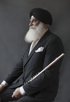 Portrait serious, well-dressed senior man in turban holding flute
