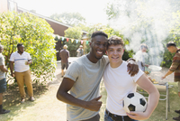 Portrait confident young men with soccer ball enjoying backyard barbecue