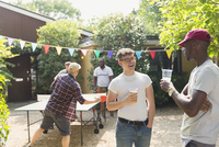 Male friends drinking beer and playing ping pong in summer backyard 11086048066| 写真素材・ストックフォト・画像・イラスト素材|アマナイメージズ