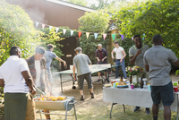 Male friends playing ping pong, enjoying backyard barbecue 11086048074| 写真素材・ストックフォト・画像・イラスト素材|アマナイメージズ