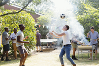 Male friends playing soccer and ping pong, enjoying backyard barbecue 11086048080| 写真素材・ストックフォト・画像・イラスト素材|アマナイメージズ