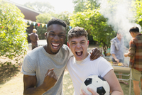 Portrait enthusiastic young men with soccer ball cheering, enjoying back yard barbecue