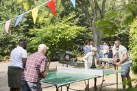 Male friends playing ping pong in sunny back yard 11086048093| 写真素材・ストックフォト・画像・イラスト素材|アマナイメージズ