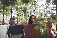 Smiling woman hanging clothing on campsite clothesline in woods