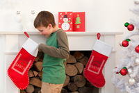 Young boy looking in Christmas stocking 11087016418| 写真素材・ストックフォト・画像・イラスト素材|アマナイメージズ