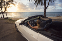USA, Hawaii, Oahu, Banzai Pipeline, Mid adult woman watching sunset in convertible car at beach 11090020209| 写真素材・ストックフォト・画像・イラスト素材|アマナイメージズ