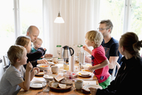Sweden, Family with children (2-3, 4-5,10-11,16-17) eating breakfast at table
