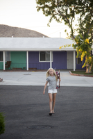 USA, California, Girl (12-13) carrying skateboard with motel in background 11090021219| 写真素材・ストックフォト・画像・イラスト素材|アマナイメージズ