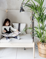 Sweden, Girl (4-5) sitting on bed and looking at pictures of butterflies in book 11090021264| 写真素材・ストックフォト・画像・イラスト素材|アマナイメージズ