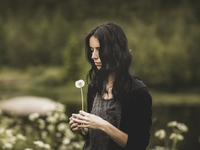 Young woman with dandelion in Sweden