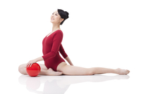 Female rhythmic gymnast performing with ball