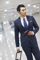 Young businessman walking in airport with suitcase 11091009897| 写真素材・ストックフォト・画像・イラスト素材|アマナイメージズ