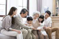 Happy Chinese family looking at photo album on sofa