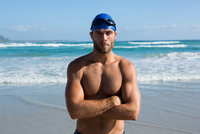 Portrait of shirtless athlete standing at beach