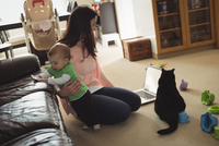 Mother holding her daughter while using laptop in living room 11092006544| 写真素材・ストックフォト・画像・イラスト素材|アマナイメージズ