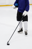 Low section of player with hockey stick at ice rink 11092008894| 写真素材・ストックフォト・画像・イラスト素材|アマナイメージズ