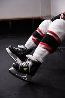 Low section of player wearing ice skates relaxing in dressing room 11092008903| 写真素材・ストックフォト・画像・イラスト素材|アマナイメージズ