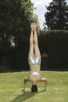 A young woman doing a handstand on grass, balancing on her head. Back view.