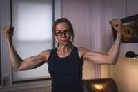 A strong woman with toned arms and clenched fists.