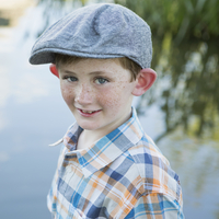 A young boy wearing a checked shirt and cloth cap with a large brim standing on a riverbank.