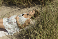 A pregnant woman lying in the sun in the sand dunes. Taking it easy.