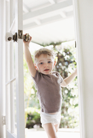 Young boy wearing T-Shirt and pants opening a door. 11093006079| 写真素材・ストックフォト・画像・イラスト素材|アマナイメージズ