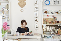 A woman sitting at a desk in a small gift shop, doing the paperwork, managing the business, using a laptop and a smart phone.  11093006296| 写真素材・ストックフォト・画像・イラスト素材|アマナイメージズ