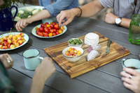 A group of people gathered around a table with plates of fresh fruits and vegetables, and a round cheese and salami on a choppin 11093006617| 写真素材・ストックフォト・画像・イラスト素材|アマナイメージズ