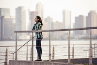 A woman standing on the waterfront, view to the city over the water in New York City.  11093006790| 写真素材・ストックフォト・画像・イラスト素材|アマナイメージズ