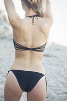 Blond woman in a black bikini on a sandy beach.
