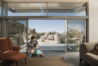 A man and a young child in an ecohouse, a home with large glass walls and view out over the rocky landscape.