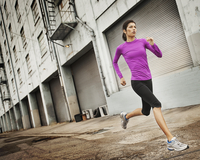A woman running along an urban road with her arms working, stretching her legs.