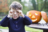 A boy looking through his curved fingers beside a carved pumpkin lantern,  11093008436| 写真素材・ストックフォト・画像・イラスト素材|アマナイメージズ