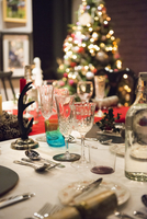 A table laid for a Christmas meal, with silver and crystal glasses and a Christmas tree in the background.  11093008469| 写真素材・ストックフォト・画像・イラスト素材|アマナイメージズ
