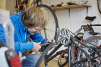 A young man working in a cycle shop, repairing a bicycle.  11093008506| 写真素材・ストックフォト・画像・イラスト素材|アマナイメージズ
