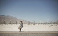 A young woman with a suitcase standing on the edge of the highway.  11093008681| 写真素材・ストックフォト・画像・イラスト素材|アマナイメージズ