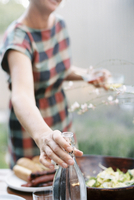A woman holding two glasses and reaching for a bottle of wine. 11093009008| 写真素材・ストックフォト・画像・イラスト素材|アマナイメージズ