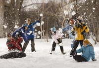 Four people outdoors in hats, coats and scarves, having an energetic snowball fight.