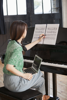 Young woman sitting at a grand piano in a rehearsal studio, annotating sheet music. 11093009659| 写真素材・ストックフォト・画像・イラスト素材|アマナイメージズ