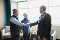A man greeting a mature couple in an office.  11093009668| 写真素材・ストックフォト・画像・イラスト素材|アマナイメージズ